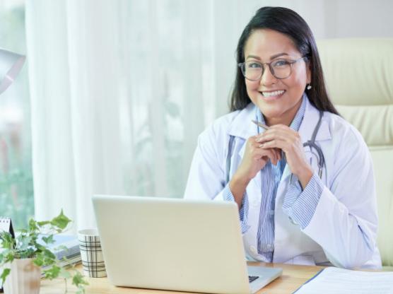 smiling-ethnic-doctor-sitting-desk-office_1098-21303